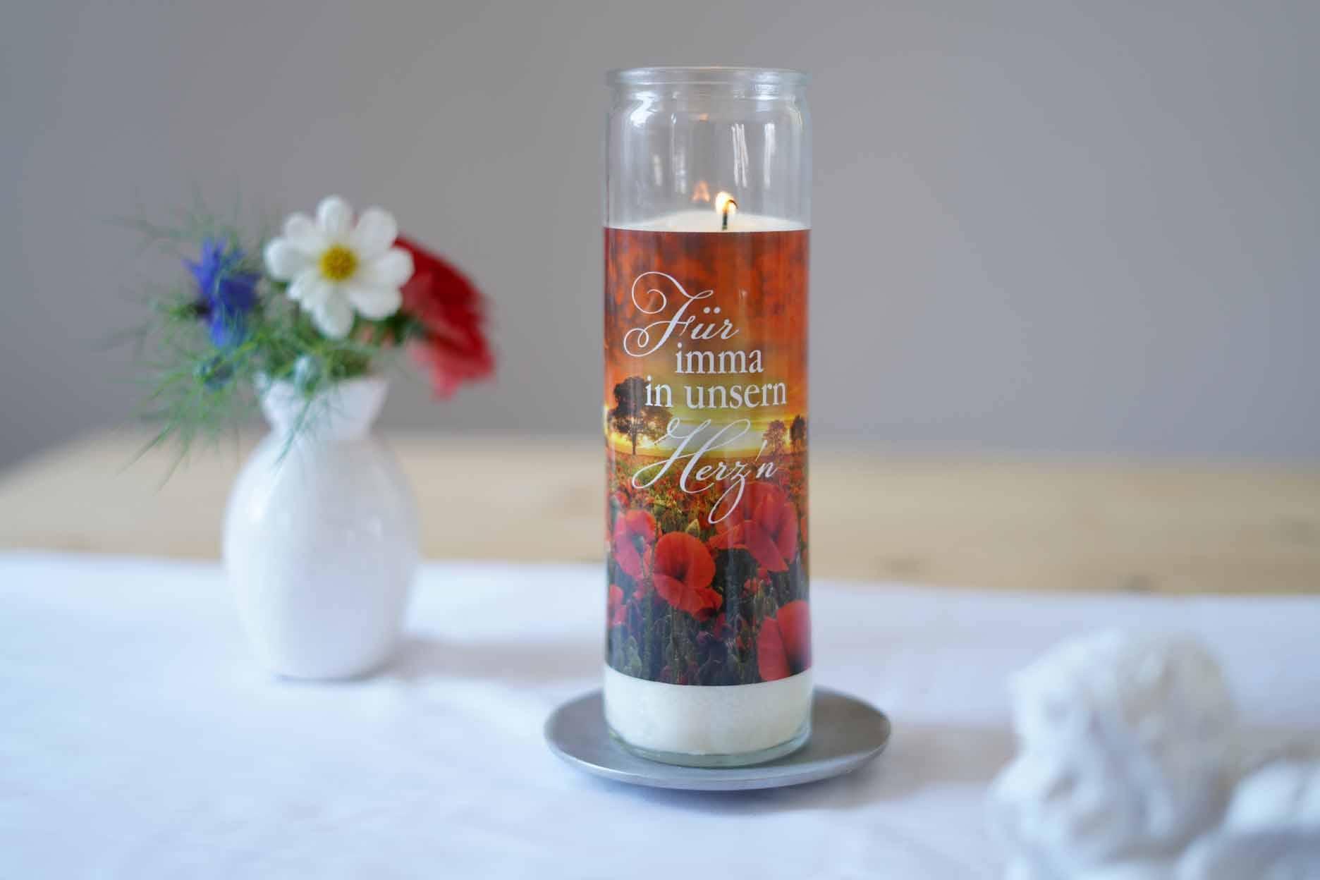 Gedenkkerze im Glas mit Blumen auf einem Tisch