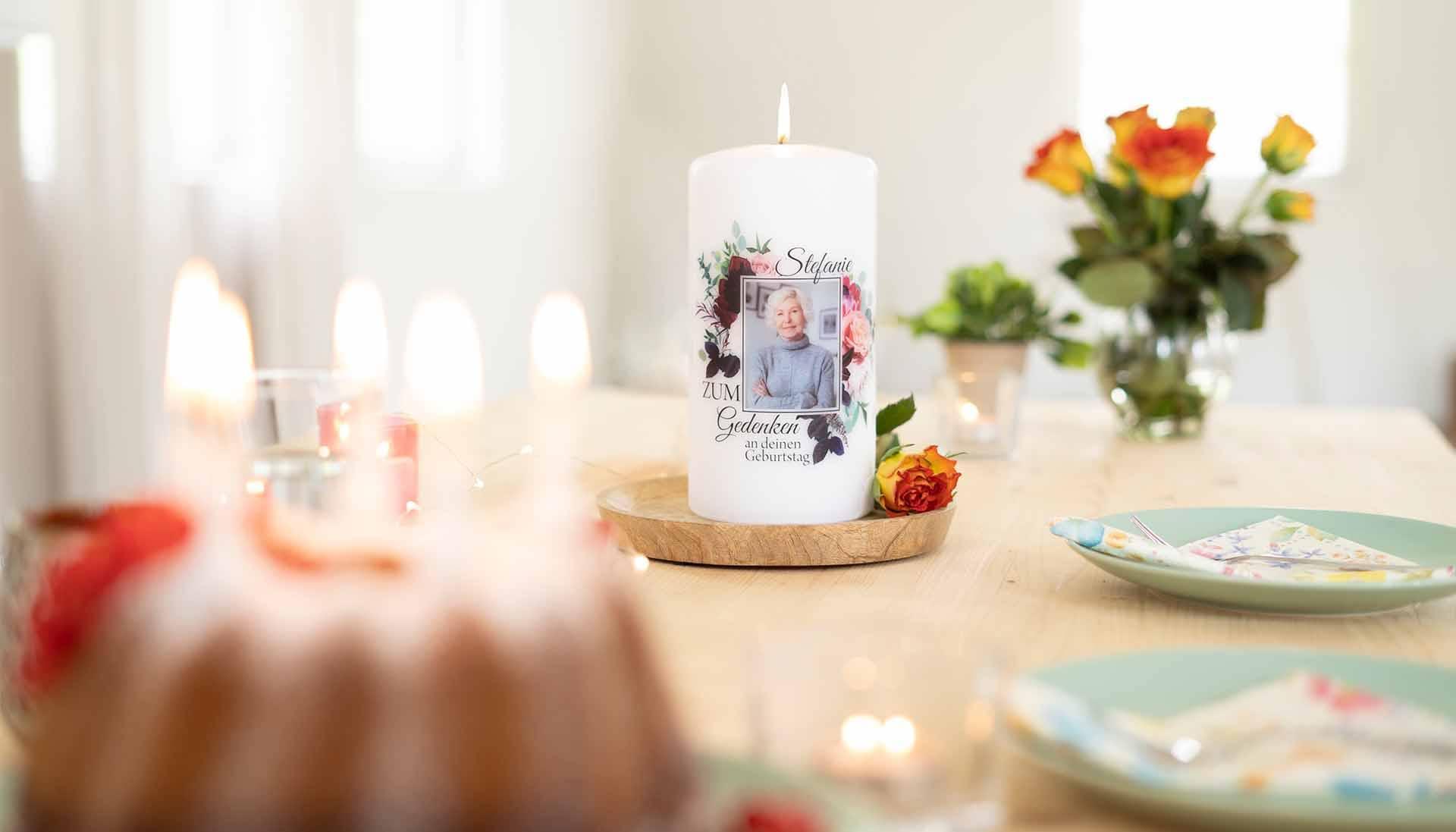 individuelle Gedenkkerze zum Gedenken am Geburtstag auf einem gedeckten Holztisch