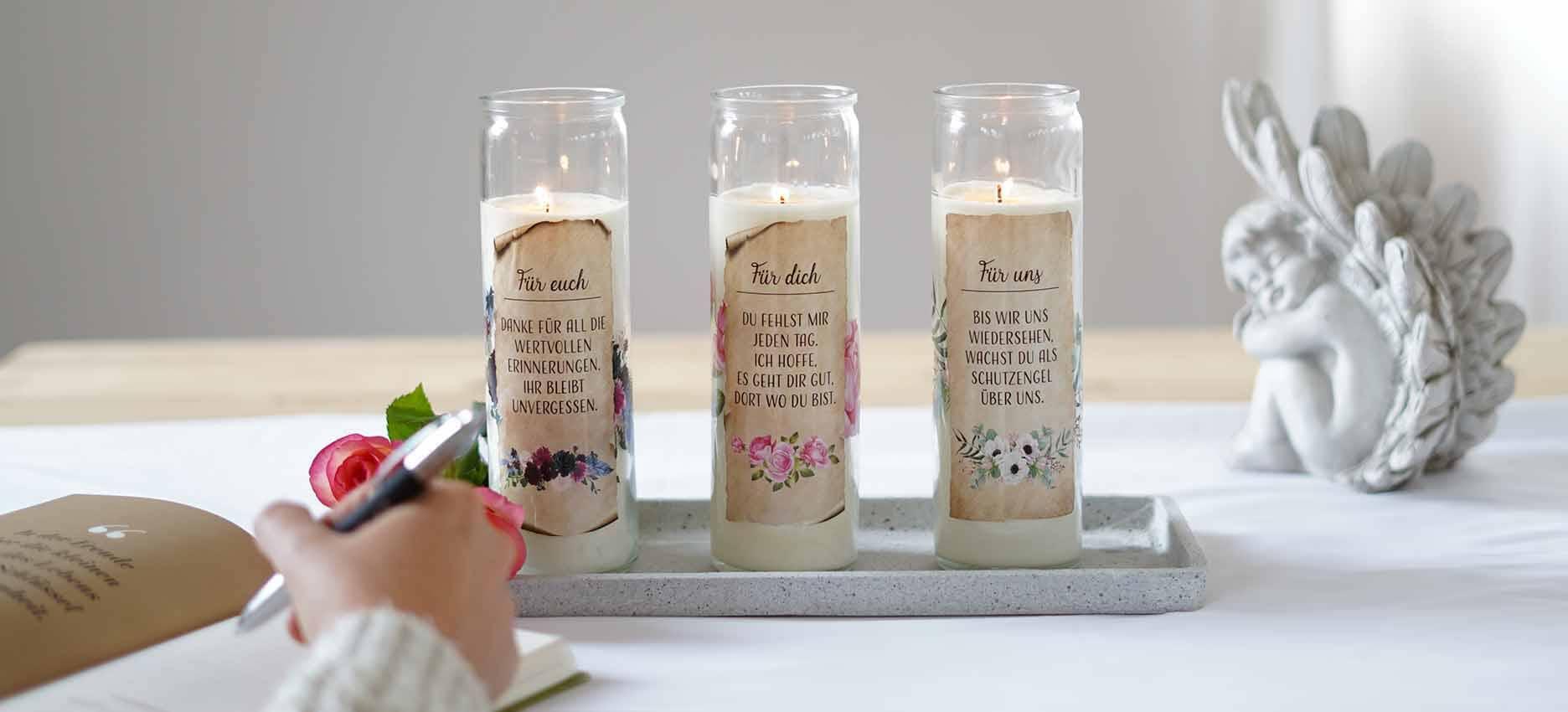 Gedenkkerzen mit Blumen-Motiven auf einem Kerzenteller