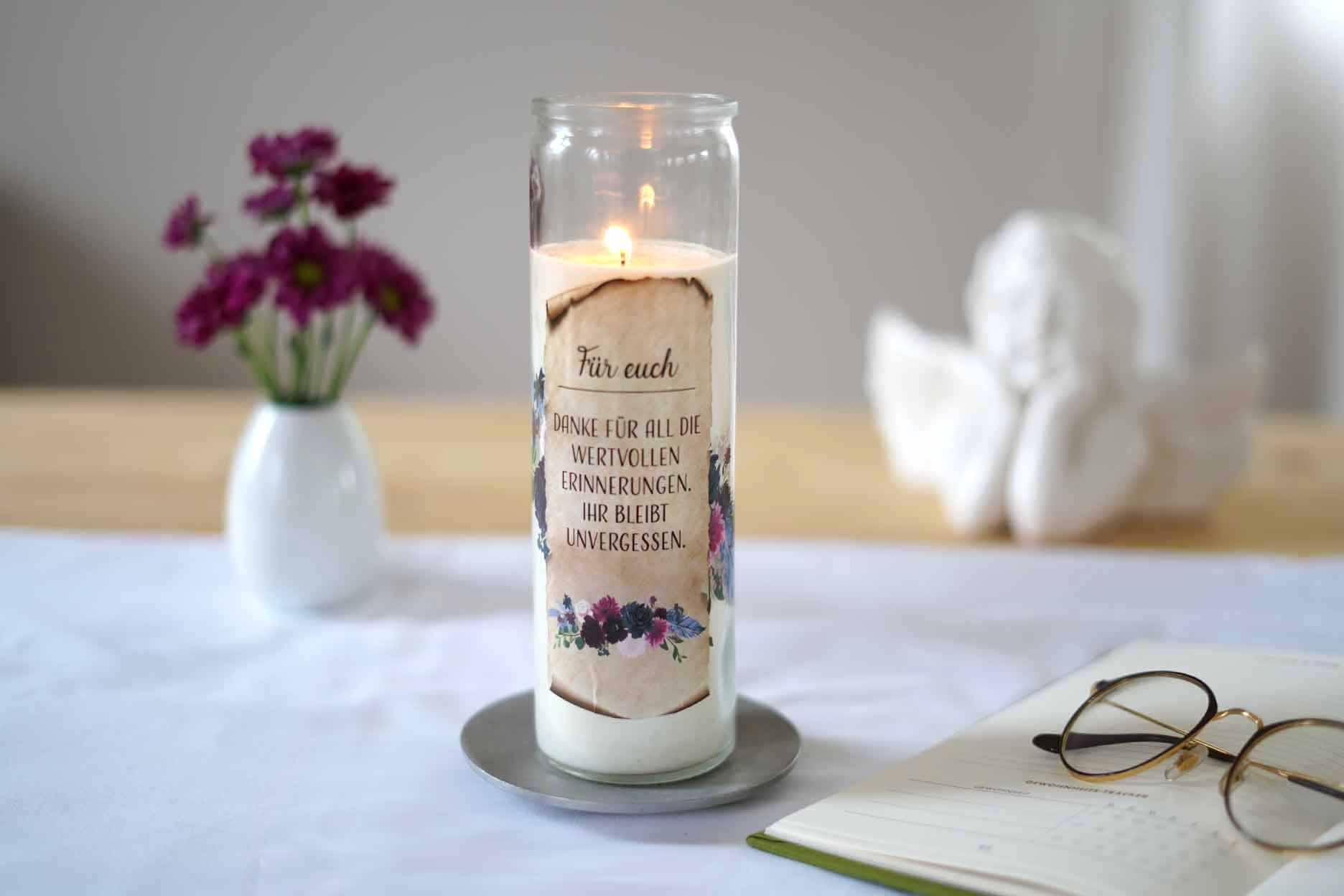 Gedenkkerze neben einem Buch und violetten Blumen auf einem Tisch