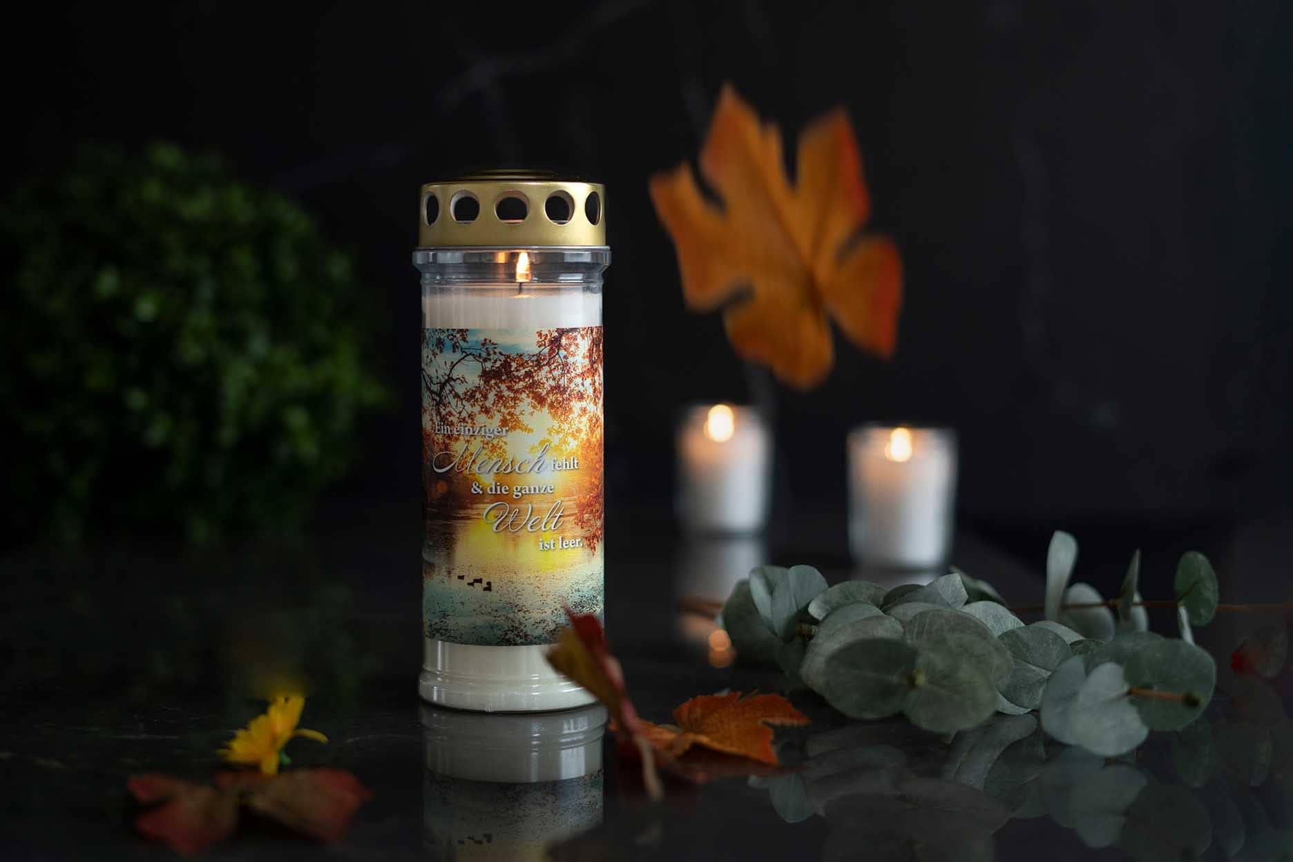 Grabkerze wird neben anderen Kerzen am Grab angezündet