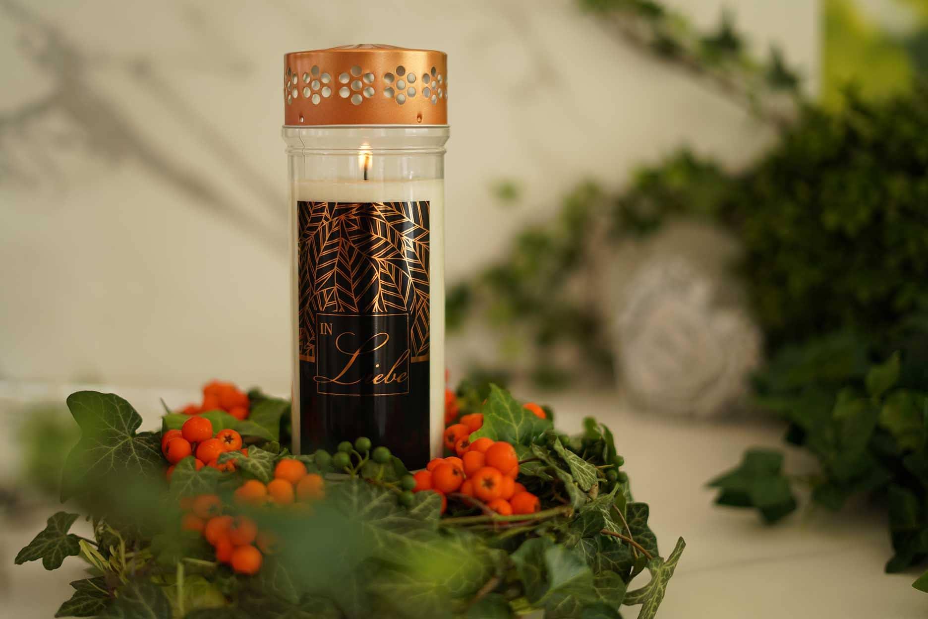 Allerheiligen Gesteck aus Efeu und Beeren auf einem hellen Grabstein