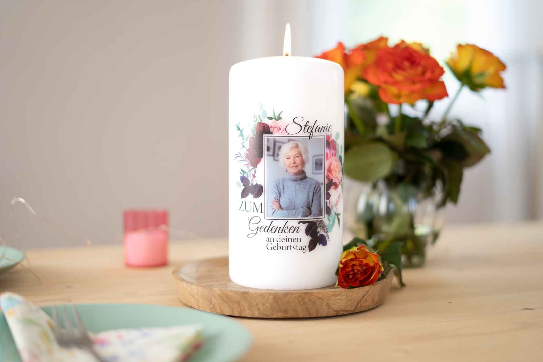 eine selbstgestaltete Gedenkkerze auf einem Tisch neben einem Blumenstrauß