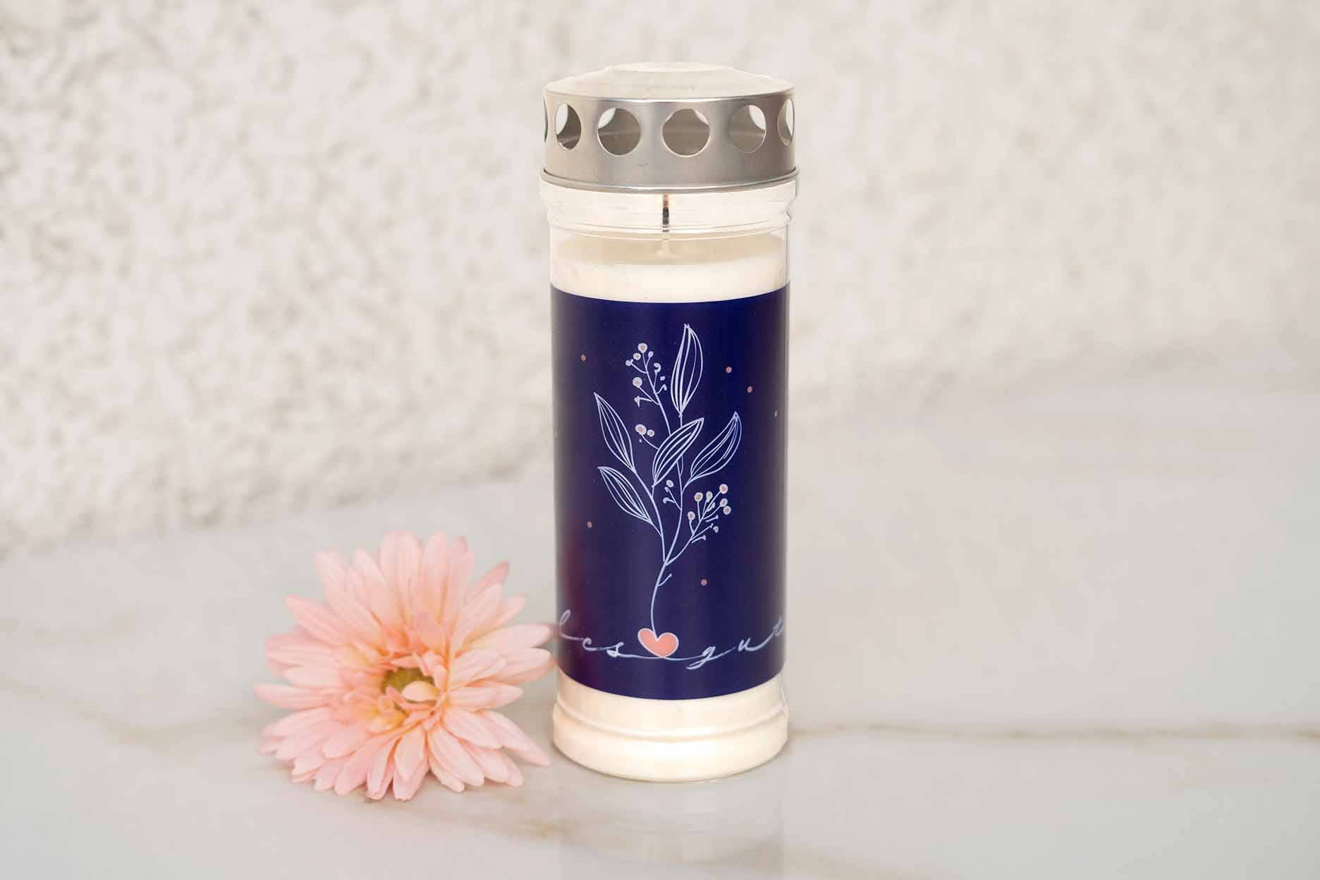 eine Grabkerze mit blauem Motiv und einer rosa Blume auf einer Marmorplatte