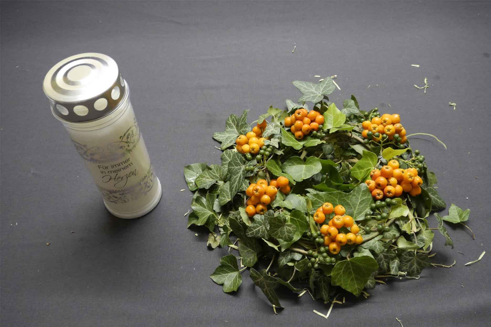Herbstliche Dekoration Grabschmuck Styroporkranz mit Holzwolle Efeu und Vogelbeeren dekoriert