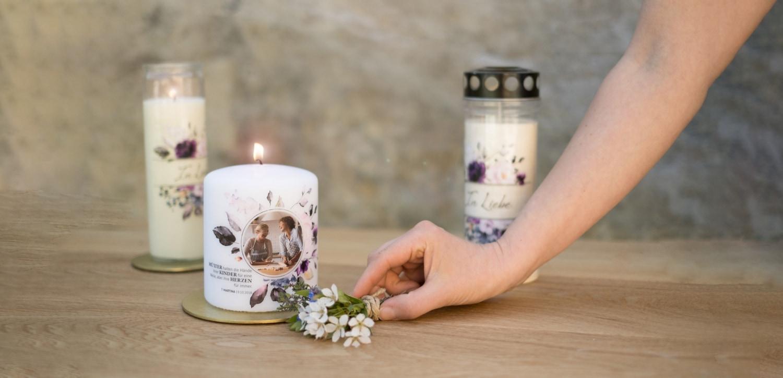 Gedenkkerzen und eine Grabkerze für den Muttertag auf einem Tisch aus Holz